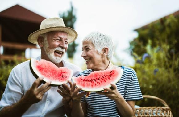 възрастни мъж и жена ядат диня